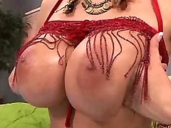 Chesty chick plays with tits on bed